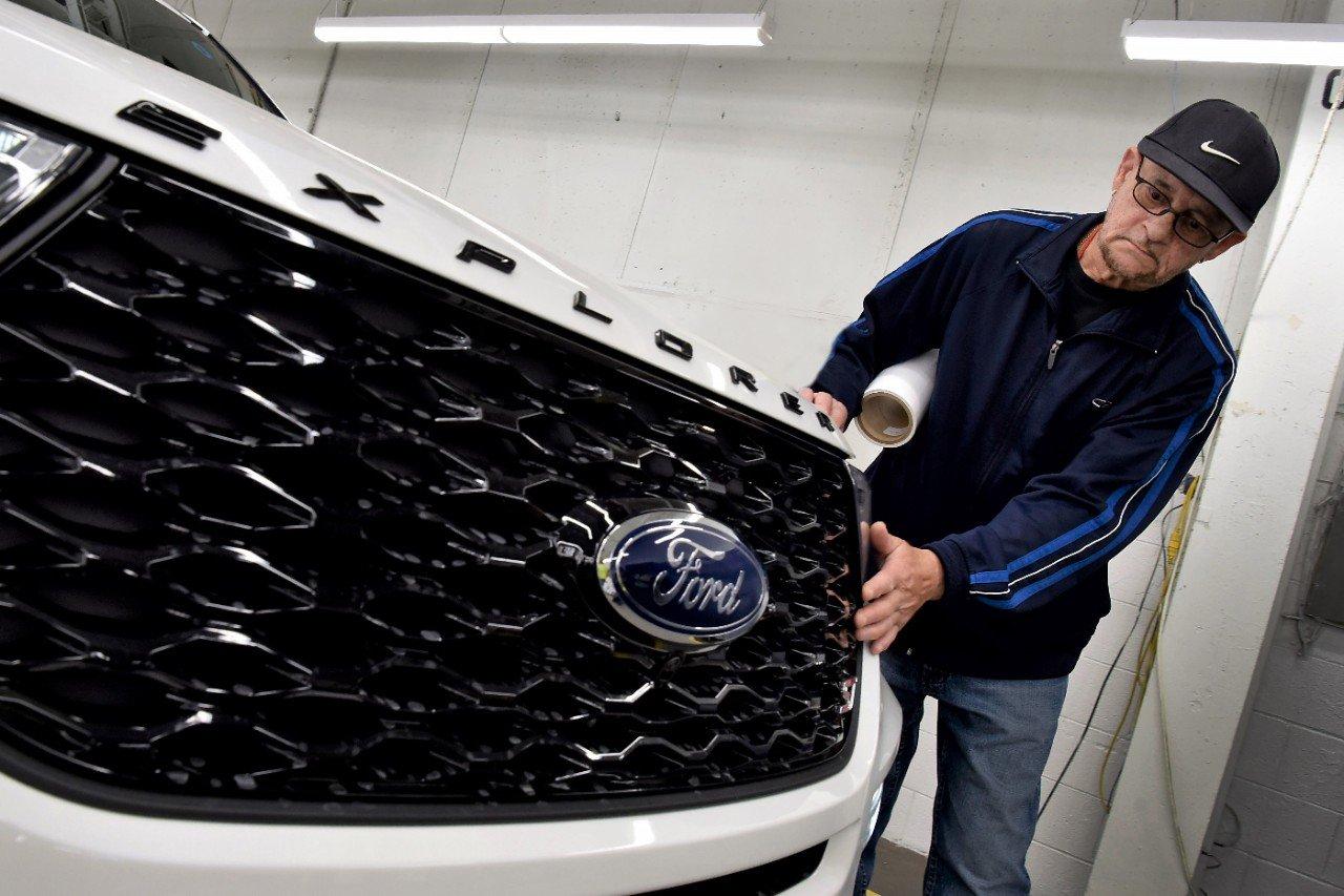 Frente de um dos SUVs da Ford com o logotipo em detalhe e uma pessoa verificando