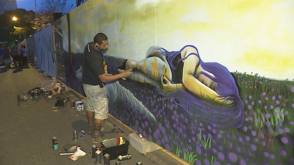 Artista faz obra em tapume da Praça da Liberda, em Belo Horizonte — Foto: Reprodução/TV Globo