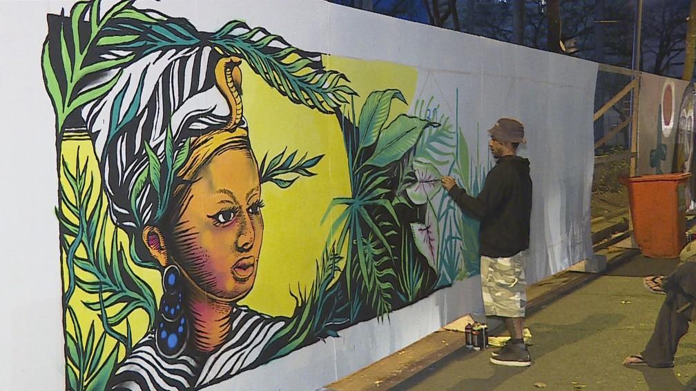 Artista trabalha em tapumes da Praça da Liberdade, em BH — Foto: Reprodução/TV Globo